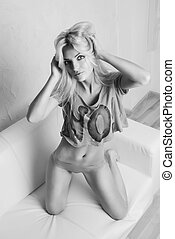 Pretty sexy young blonde woman sitting on armchair