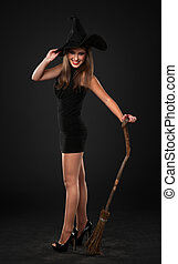 sexy young brunette witch with a broom