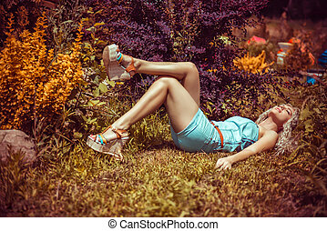 Pretty sexy young woman lying on grass