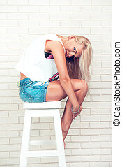 Pretty sexy young woman with blonde hair on chair