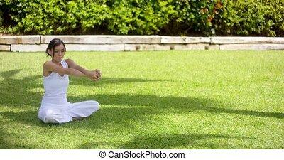 Pretty single woman in empty yard stretching arms - Pretty...