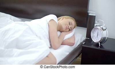 Pretty Sleeping Woman with Alarm Clock Next to Her - Close...