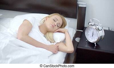 Pretty Sleeping Woman with Alarm Clock Next to Her