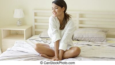 Pretty slender woman relaxing on her bed in a clean white...