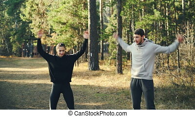 Pretty slim girl and bearded guy are exercising outdoors...