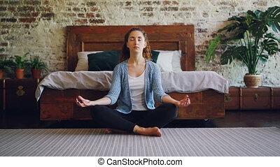 Pretty slim girl with long hair is relaxing in lotus pose...