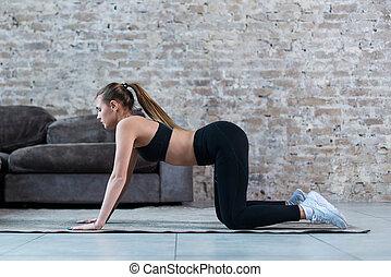 Pretty slim sportswoman practicing gymnastics doing...