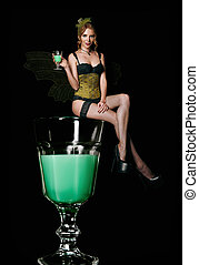 Pretty sly green fairy sitting on glass of absinthe. ...