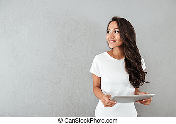 Pretty smiling asian woman holding tablet computer