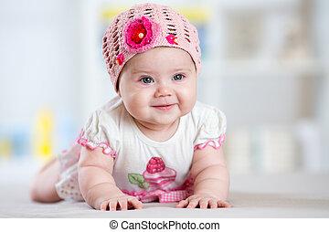 smiling baby girl lying on her belly in nursery room