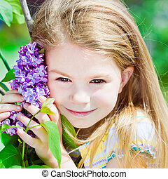 Pretty smiling blond little girl with blooming lilac