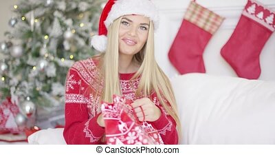 Pretty smiling blondie looking inside her christmas bag gift while sitting on sofa in her perfectly decorated home. She is quite surprised what she got.