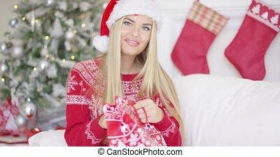 Pretty smiling blondie looking inside her christmas gift -...
