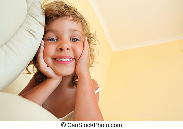 pretty smiling little girl in cosy room, foreshortening from below