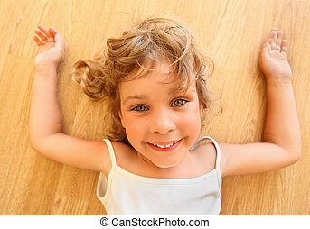 pretty smiling little girl lies on floor