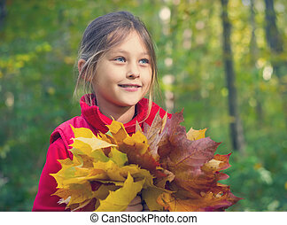Pretty smiling little girl with maple leaves