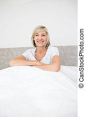 Pretty smiling mature woman sitting on bed