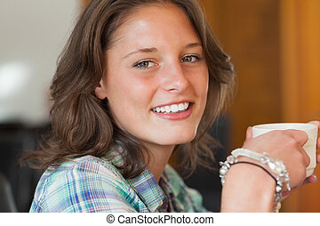 Pretty smiling student having a cup of coffee