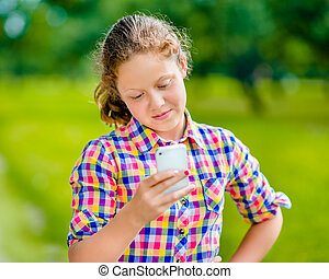 Pretty smiling teenage girl in casual clothes with smartphone in her hand, looking at screen, reading a message, using Facebook in sunny day in summer park