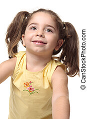 Beautiful radiant smiling toddler girl looking up. She has pigtails and is wearing a yellow tank top with embroidery.