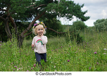 Pretty smiling toddler girl with blond curly hair wearing wildflowers wreath walking in the countryside