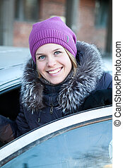 Pretty smiling woman getting in the new car