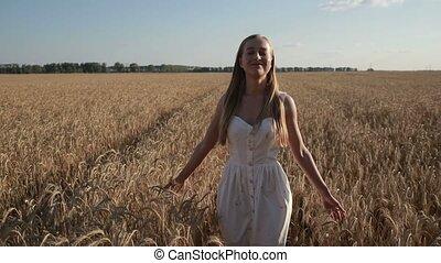 Pretty smiling woman relaxing in wheat field