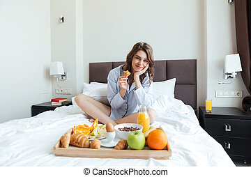 Pretty smiling woman sitting on bed and having breakfast