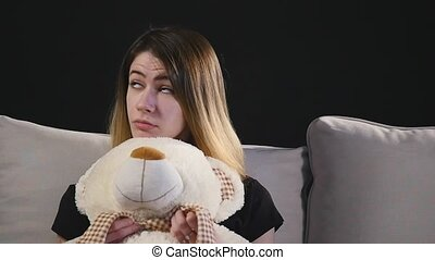 Pretty smiling woman sitting on the couch hugging teddy bear