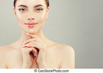 Pretty smiling woman spa model with clear skin on gray background