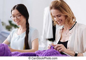 Pretty smiling women enjoying knitwork