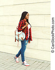 Pretty smiling young african woman with backpack walking in city