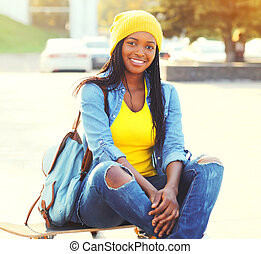 Pretty smiling young african woman with skateboard in the city