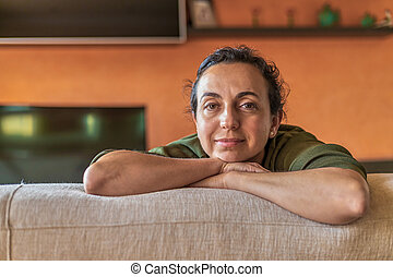 Pretty Spanish woman with glasses at home in front of the camera