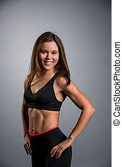 Pretty sportswoman in black top and leggings