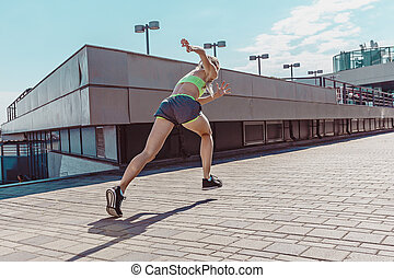 Pretty sporty woman jogging at city