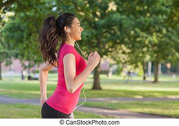 Pretty sporty woman jogging in a park