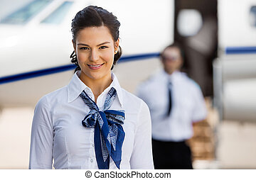 Pretty Stewardesses Smiling With Pilot And Private Jet In...