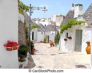 Pretty street among the trulli houses of Alberobello, Italy