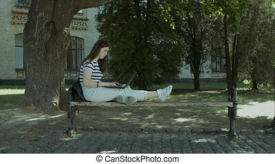 Pretty student with laptop sitting on the bench