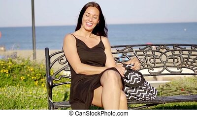 Pretty stylish woman at the seaside sitting relaxing on a...