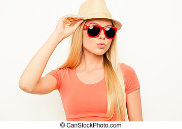 Pretty stylish woman in glasses touching her hat and pouting