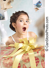 Pretty surprised girl with birthday gifts