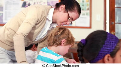 Pretty teacher helping schoolboy at his desk in elementary...