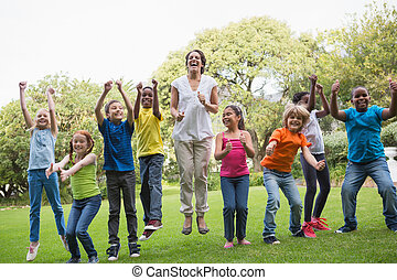 Pretty teacher jumping with pupils outside at the elementary...