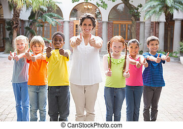 Pretty teacher standing with pupils in courtyard at the ...