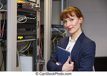 Pretty technician smiling at camera beside open server holding t