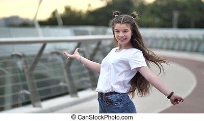 Pretty teen girl cheerfully dancing on footbridge - Close-up...