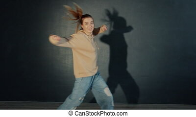 Pretty teen girl is dancing in dark studio performing beautiful creative dance alone having fun, performer is wearing trendy youth clothing. People and hobby concept.