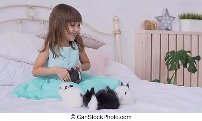 Pretty teen girl having fun, hugging and playing with decorative rabbit